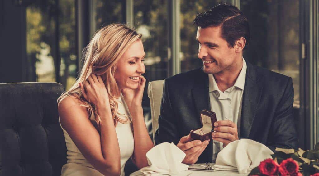 A man holding a box with a diamond engagement ring, making propose to his girlfriend